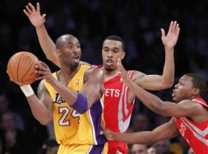 Los Angeles Lakers Kobe Bryant passes around Houston Rockets Courtney Lee and Kyle Lowry during their NBA game in Los Angeles